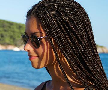 Seitenansicht einer jungen Frau mit Rastabraids und Sonnenbrille