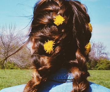 Braunhaariges Mädchen mit Flechtfrisur und Blumen im Haar