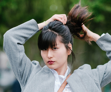 Woman putting long healthy black hair into a ponytail