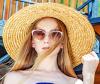 Blonde Frau mit blauem Sommerkleid, Sonnenbrille, Sonnenhut und einer Tasche aus Bast vor Treppengeländer
