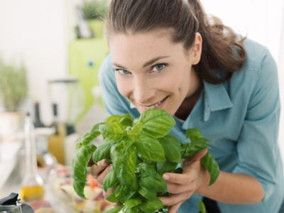 Smiling woman smelling fresh basil at home and preparing healthy food in the kitchen