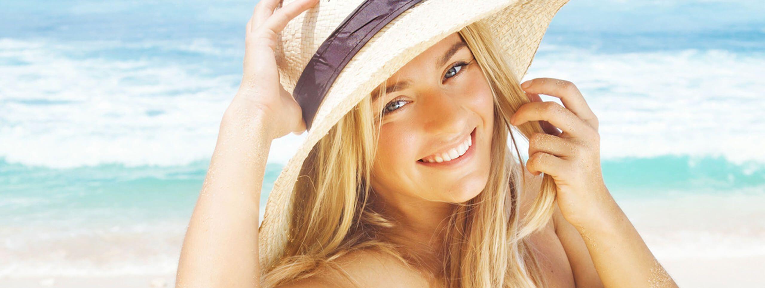 Femme blonde avec un chapeau sur la plage