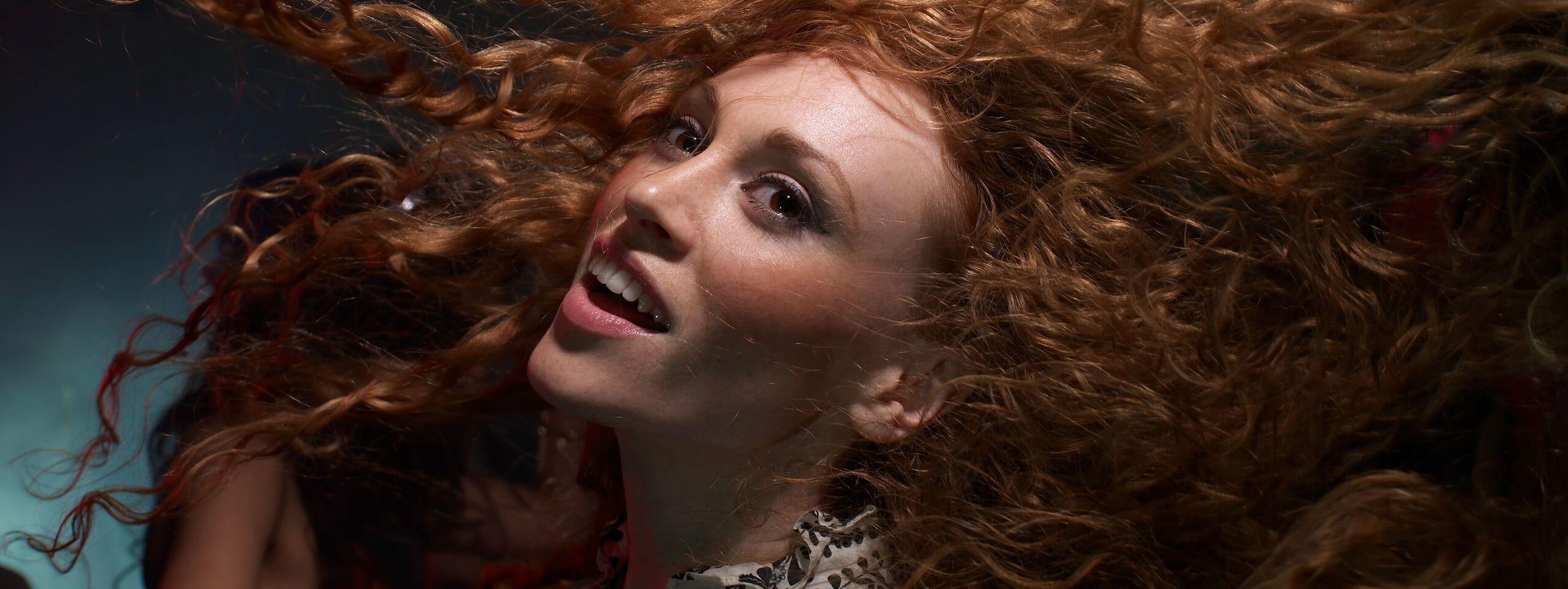 Femme rousse aux cheveux ondulés dans le vent