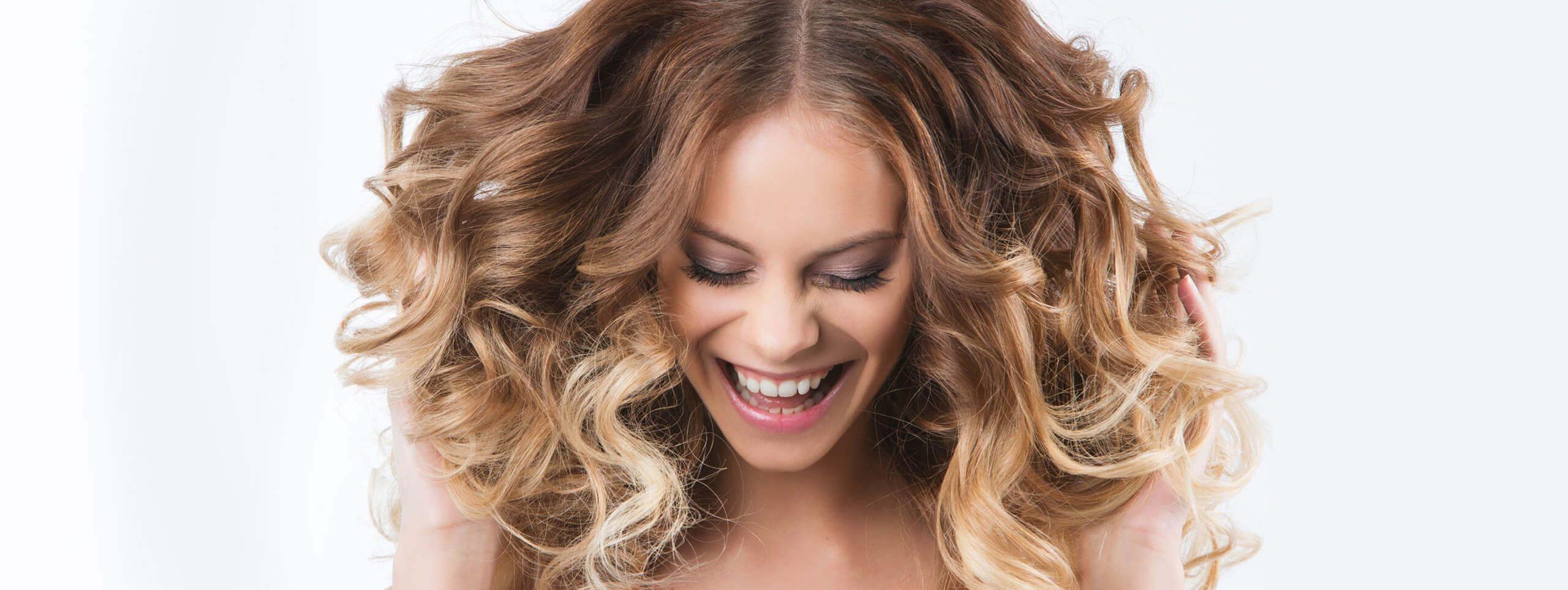 Femme souriante passant ses mains dans ses boucles