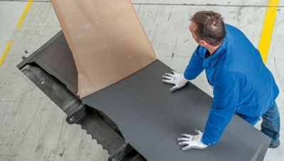 Cropped photo of two men removing adhesive film covering from an aircraft spoiler during a structural adhesive film application manufacturing process
