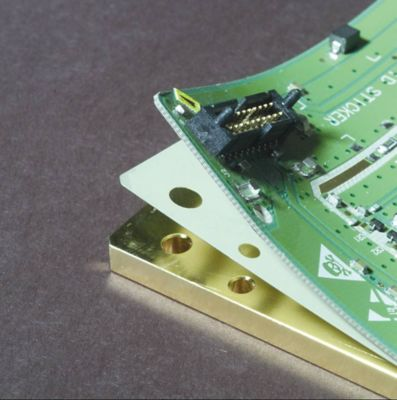 Photo of custom cut film adhesive substrate between layers of an electronic assembly green pcb is lifted to expose the layer of film