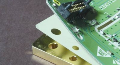 Cropped photo of custom cut film adhesive substrate between layers of an electronic assembly green pcb is lifted to expose the layer of film