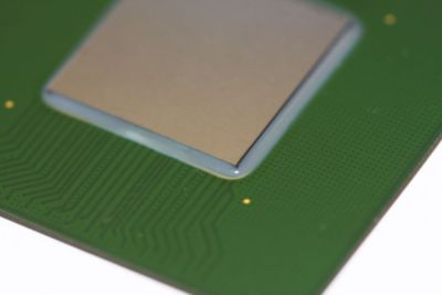 Closeup photo of flip chip underfill on a green printed circuit board