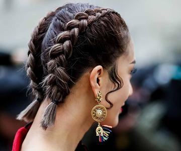 : Frau mit kurzen Haaren und Flechtfrisur sowie Ohrringen