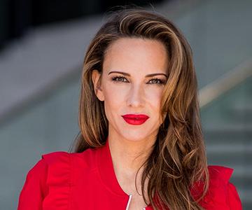 Frau mit langen Haaren und rotem Blazer