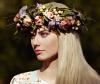Frau mit langen, blonden Haaren und floralem Blumenkranz
