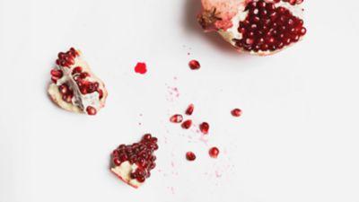 Stücke und Kerne eines Granatapfels liegen verstreut auf einem weißen Tisch.