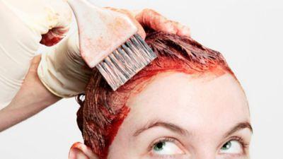 Haarfarbe von Ohren entfernen, Frau färbt sich die Haare rot mit Pinsel