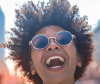 Woman with an afro smiling outside