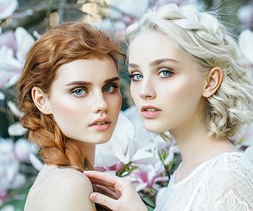 Rothaarige und weißblonde Frau tragen zwei weiße Kleider und stehen vor einem Blütenbusch, sie tragen Flechtfrisuren