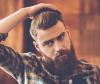 Mann mit Irokesenschnitt und Bart fährt sich mit Hand durchs Haar