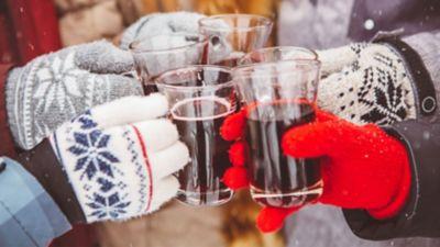 Viele Hände in kuscheligen Handschuhen stoßen mit Glühwein an.