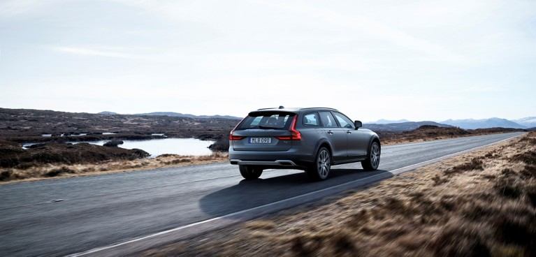 Grey Volvo sport utility vehicle driving down an empty desert road