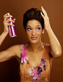 Brunette woman using hairspray