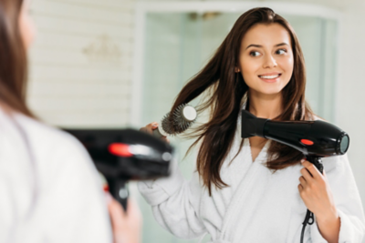Brunette woman blow drying her hair in the mirror