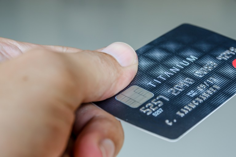 Male hand offers to pay with a credit card with an embedded chip