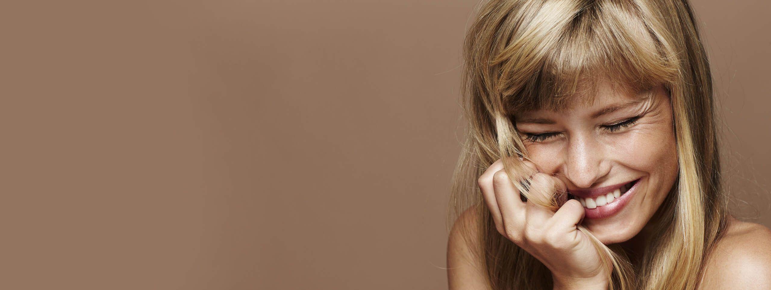 Femme blonde yeux fermés souriante