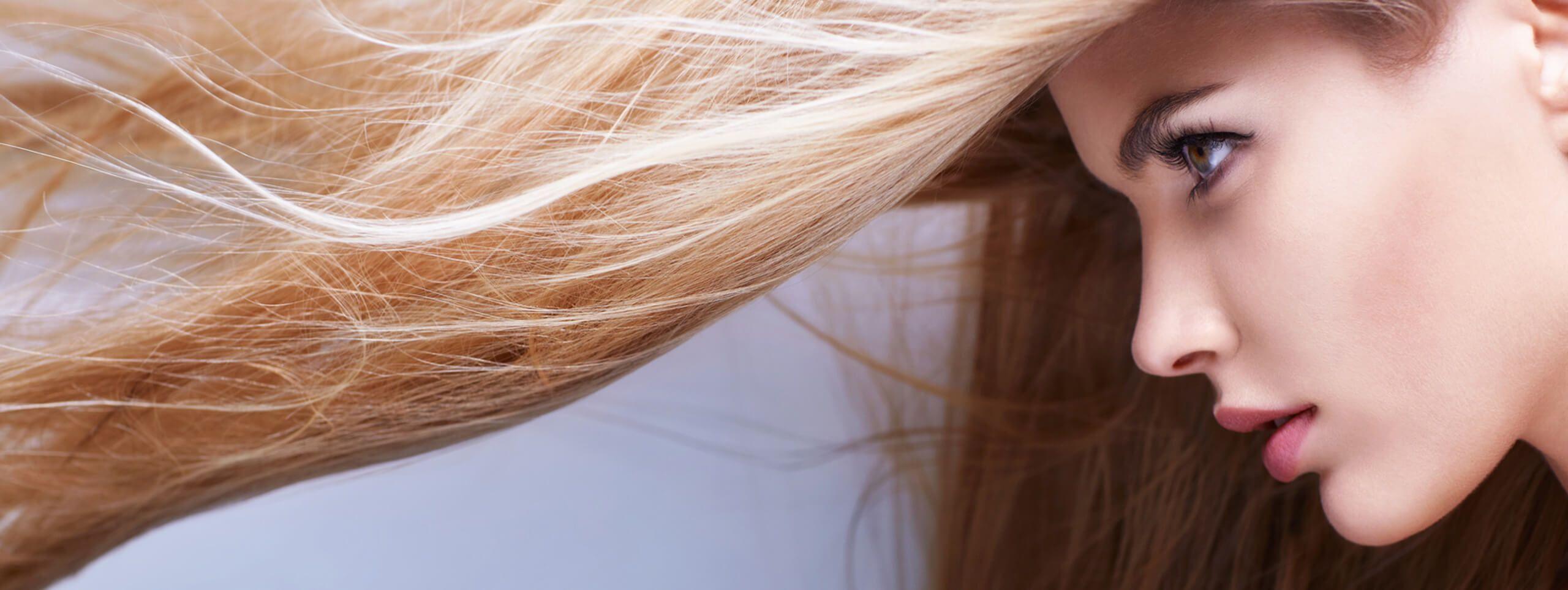 Femme blonde se séchant les cheveux