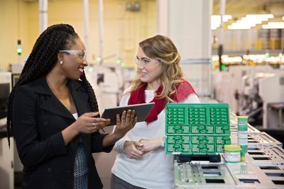 Photo of Henkel employee Hailey Kamen and Morey Corp employee Demetria Wright inside Morey Corp factory discussing henkel materials for electronic manufacturing  photo used for loctite GC10 solder promotion reference previous title Living up to promises with Morey