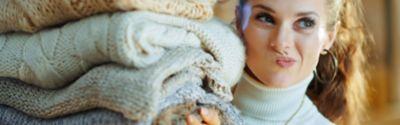 Frühjahrsputz Kleiderschrank, Frau mit einem Stapel Winterkleidung.