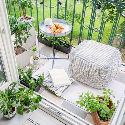 Wie du das Beste aus deinem kleinen Balkon holst, ein kleiner Balkon mit Croissants, Kaffee, einem Buch und Sitzkissen.