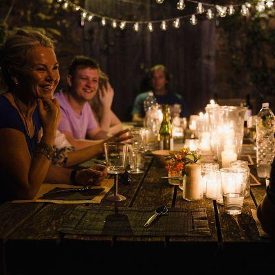 Tipps für die perfekte Gartenparty, Freunde sitzen abends im Garten am Tisch und lachen