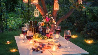 Tipps für die perfekte Gartenparty, ein dekorierter Tisch im Garten mit Beleuchtung und Kerzen im Gras