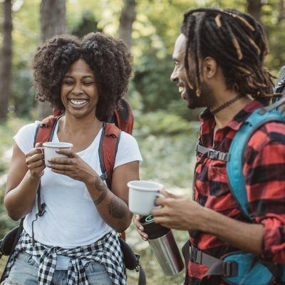 Zwei wandernde Menschen mit Rucksäcken, die eine Pause machen und sich ein Getränk teilen