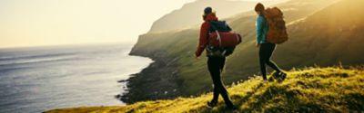 Zwei Menschen wandern durch eine Küstenlandschaft