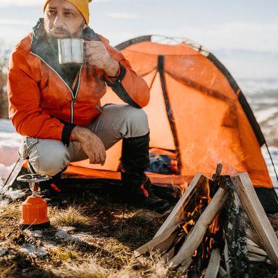 Ein Mann vor seinem Zelt mit Lagerfeuer und einem Heißgetränk in einer Tasse