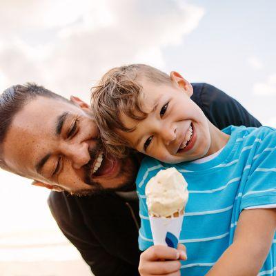 grinsendes Kind im Sommer, dreckig von Sonnencreme, Wassereis, Sand