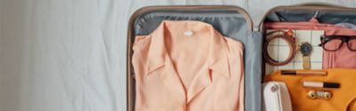 Walizka wypełniona ubraniami i innymi niezbędnymi przedmiotami