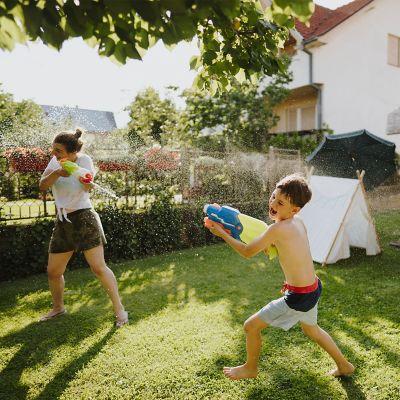 Mädchen und Junge spielen mit Wasserpistolen