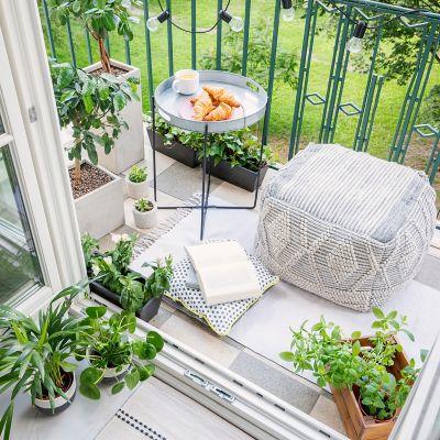 Tasse Kaffee und Teller mit Croissants auf dem Balkon