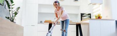 Eine in einem pinken Top gekleidete Frau saugt ihr Wohnzimmer