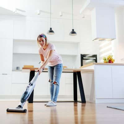 Lady in pink top vacuuming her living room