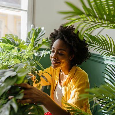 Eine in Gelb gekleidete Frau spielt mit Pflanzen