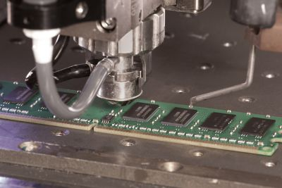 Photo of automation equipment jet dispenser dispensing underfill on a RAM memory board