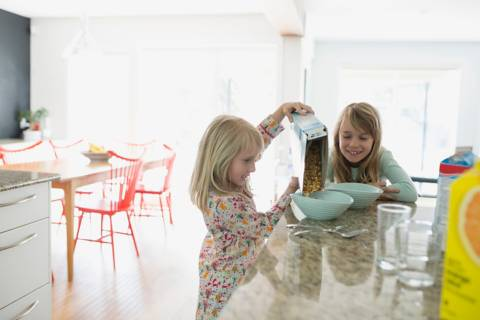 two kids in kitchen preparing breakfast with cornflakes in paper packaging