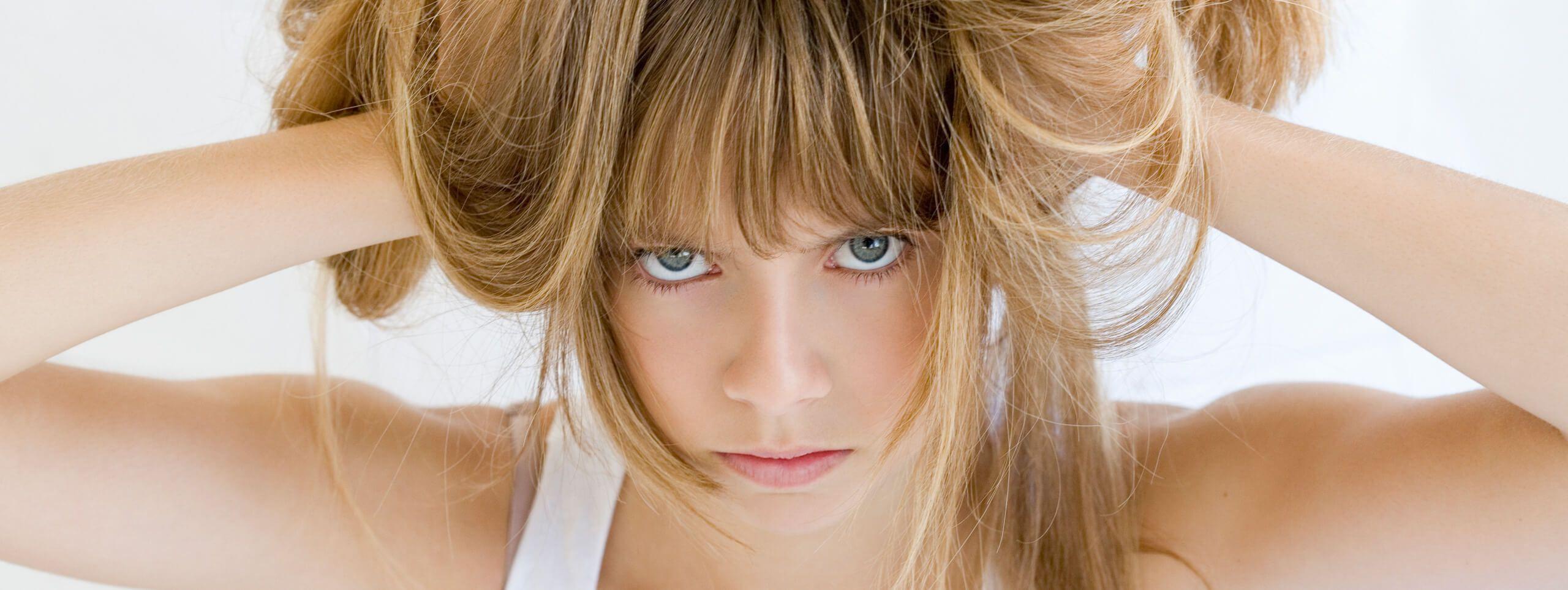 Kobieta trzymająca blond włosy z grzywką