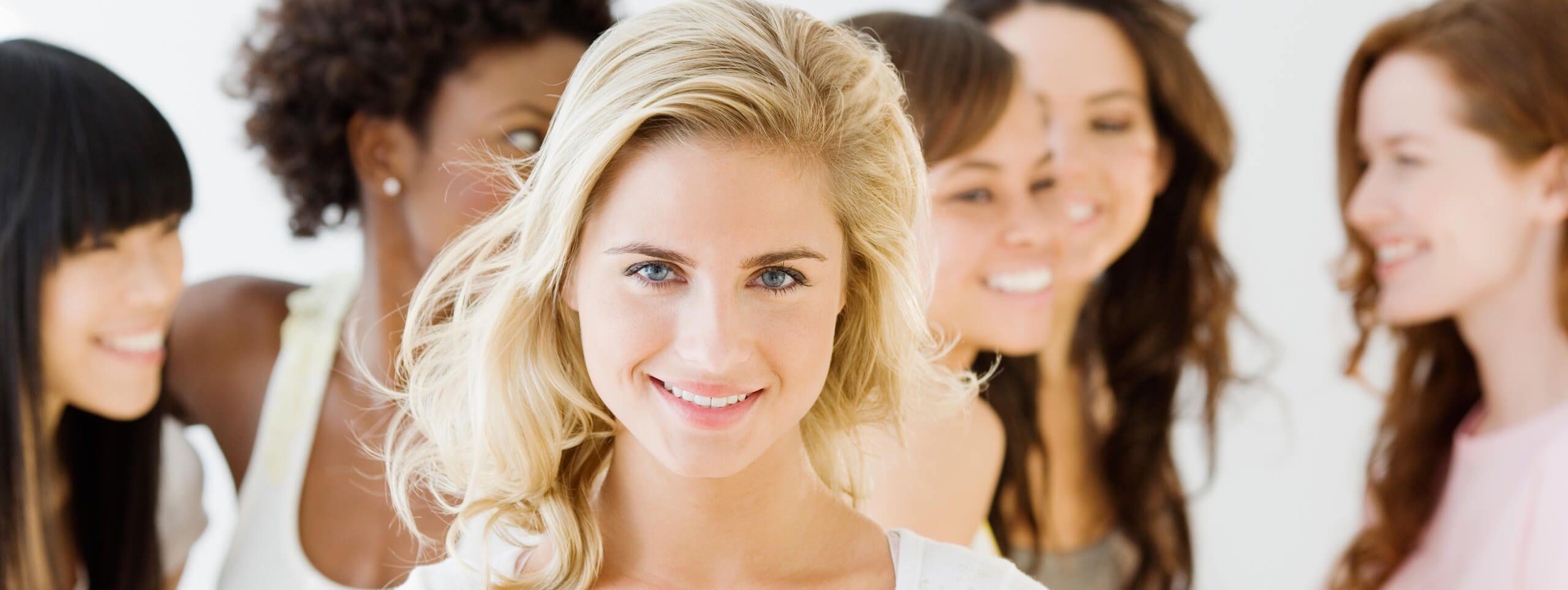 Kobieta w blond włosach na tle kobiet z ciemnymi włosami