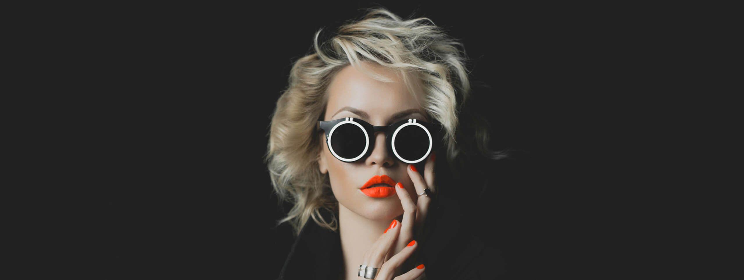 Kobieta w ciemnych okularach i krótkich blond włosach