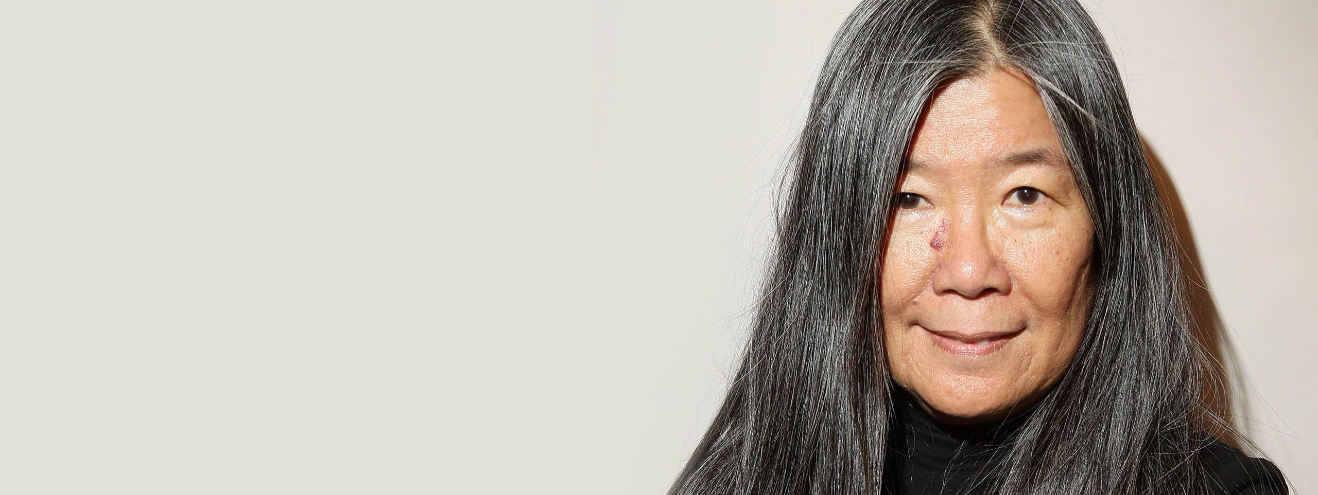 Kobieta o długich ciemno siwych włosach