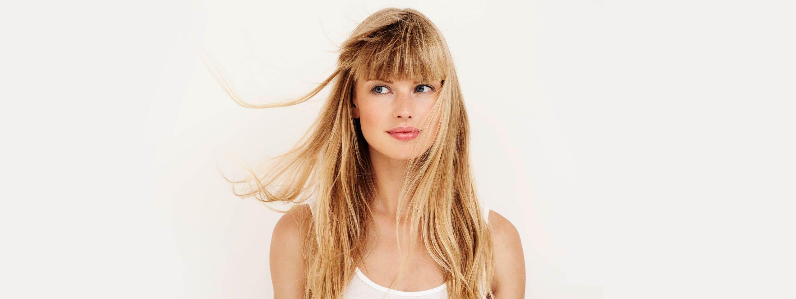 Kobieta z długimi blond włosami i grzywką