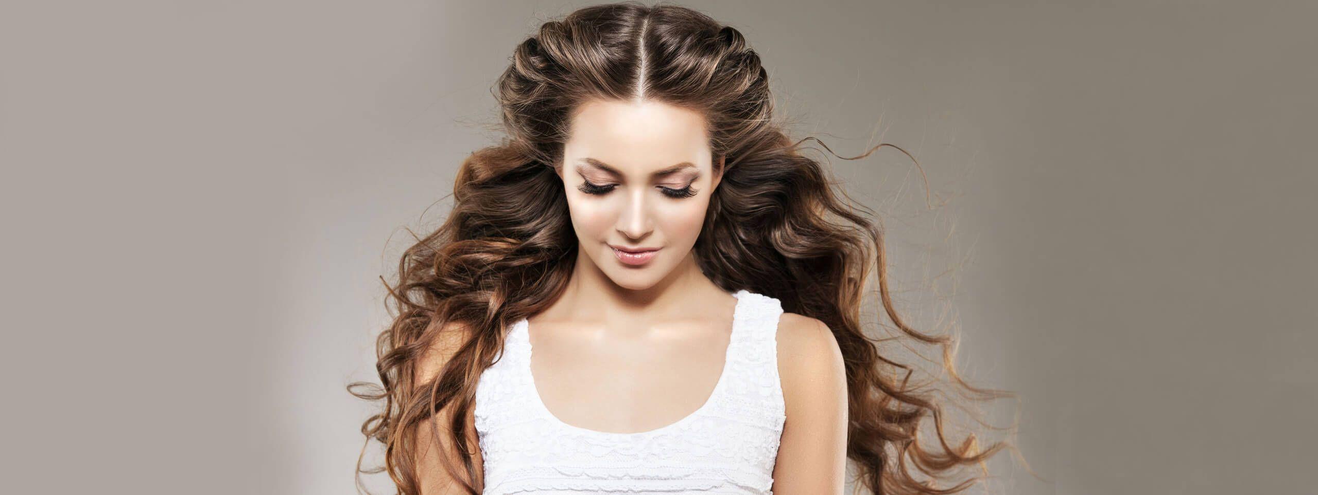 Kobieta z długimi pełnymi objętości brązowymi falowanymi włosami